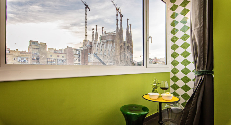 On the green wall through the window, you can look at the Sagrada Familia.