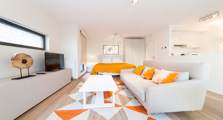 Lovely orange living room space next to the white kitchen