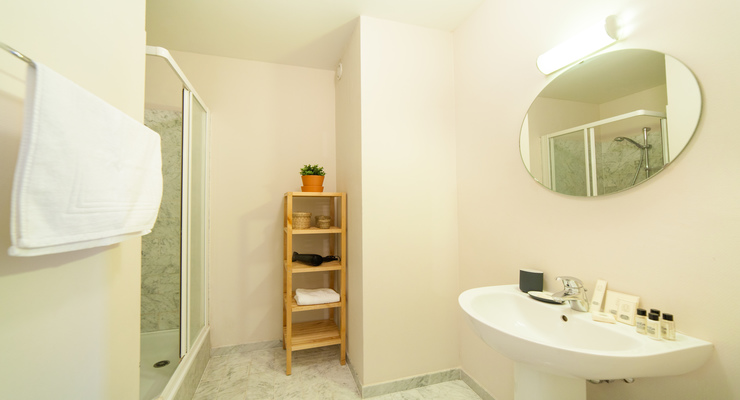 White bathroom with a mirror and sink below